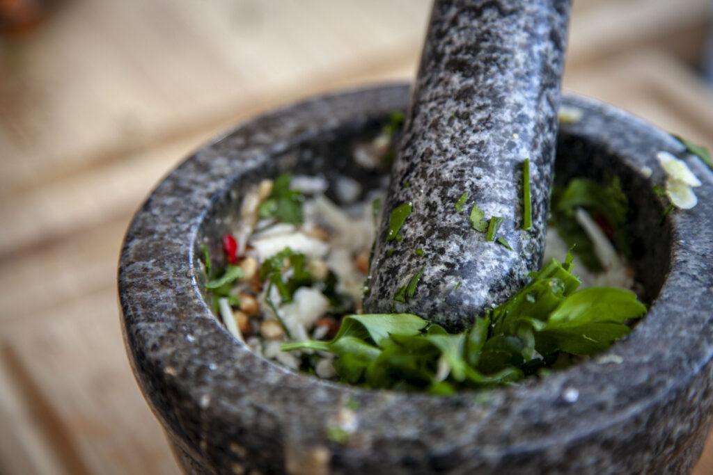 Die frischen Pesto Zutaten werden im Mörser zermahlen