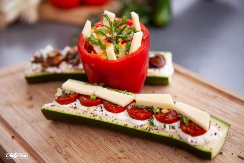 Gefüllte Paprika und gefüllte Zucchini können prima am Grill zubereitet werden.