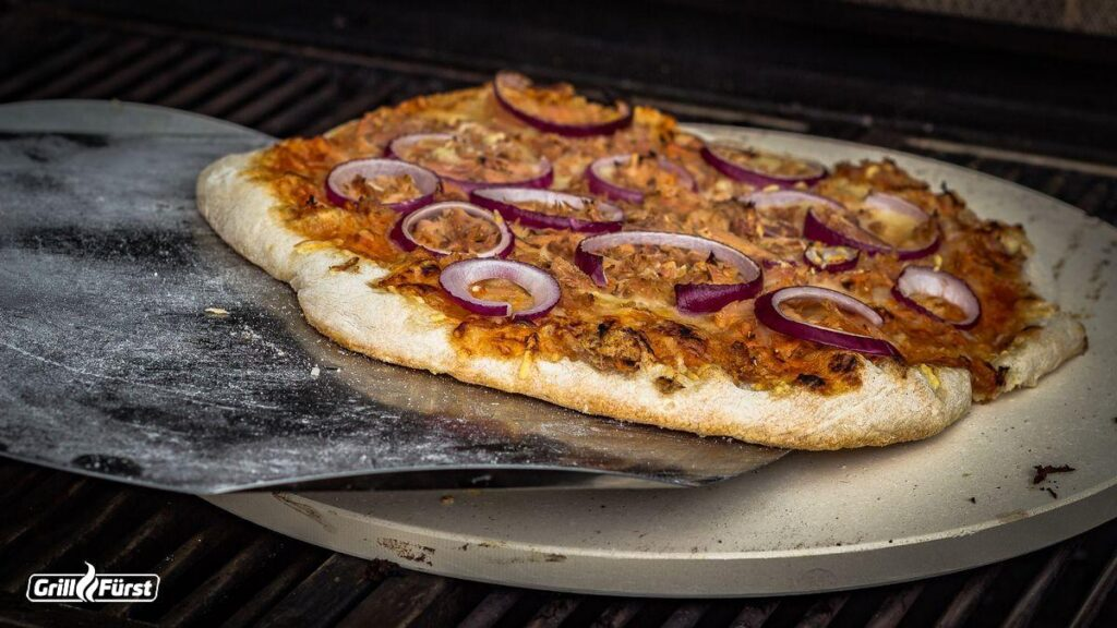 Die selbstgemachte Pizza wird auf den heissen Pizzastein gelegt