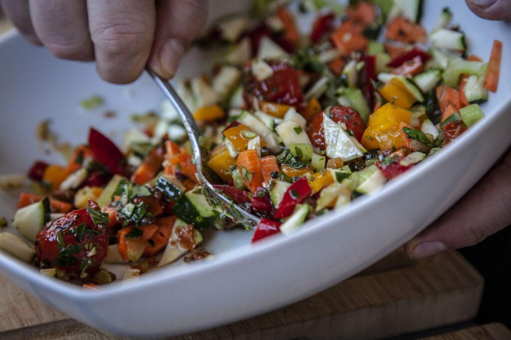 Zucchini Gemüse in einer Schüssel mit Marinade vermengen