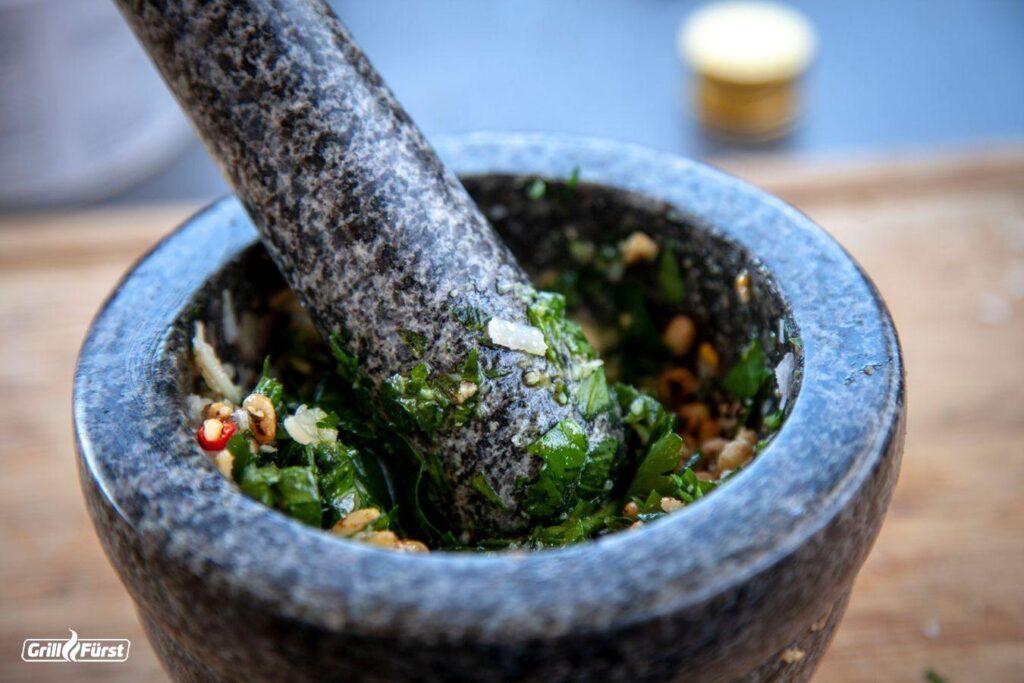 Das Pesto mit Öl und Käse im Mörser zerstampfen