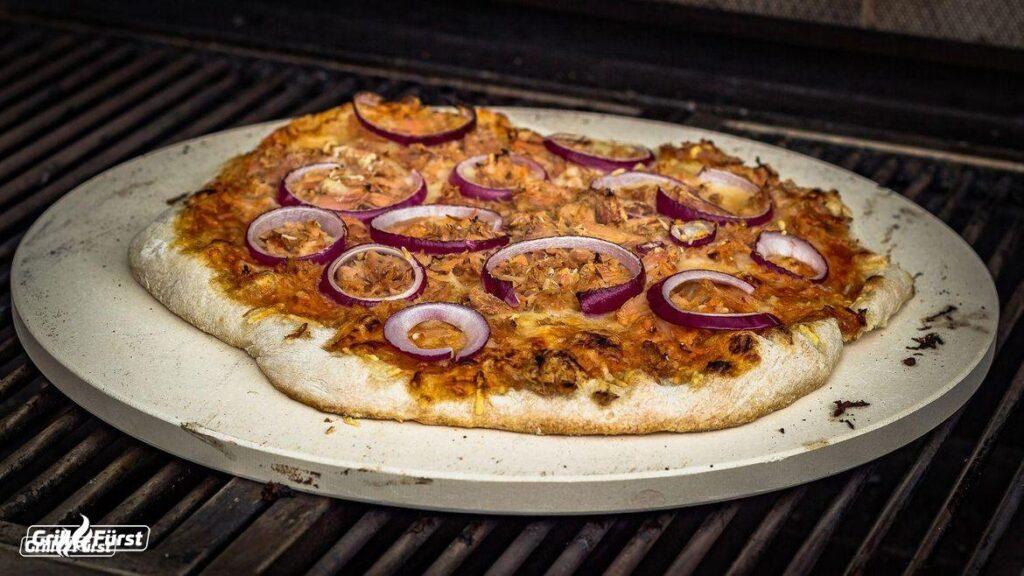 Ein Stück selbstgemachte Pizza mit saftigem Belag und knusprigem Teig sorgt für gelungene Abwechslung auf jeder Grill Party.