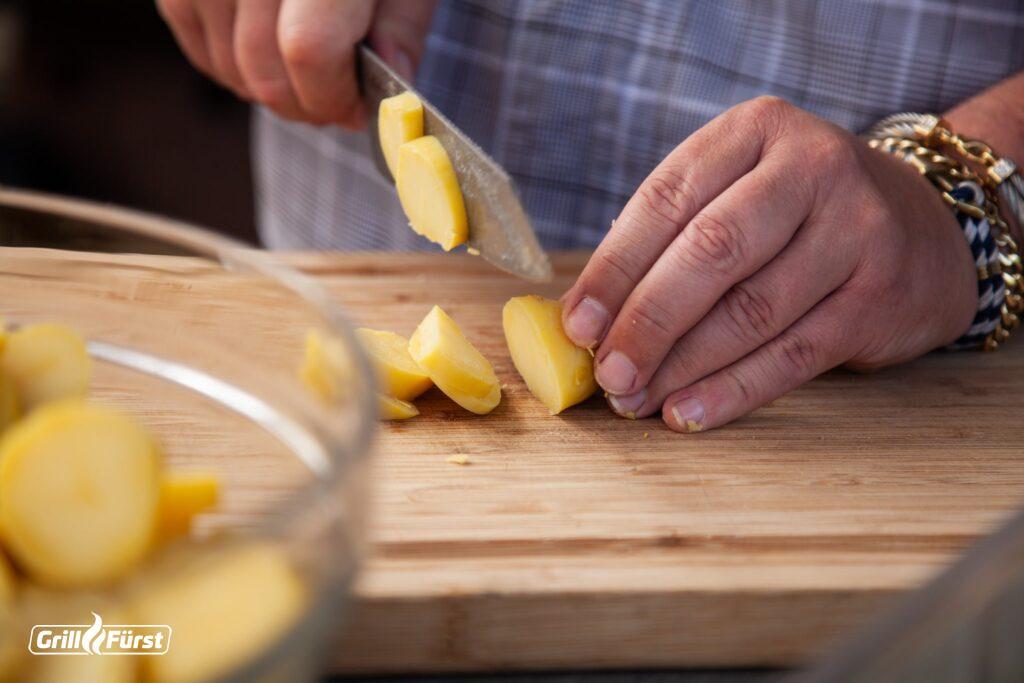 Damit der Kartoffelsalat am besten schmeckt, sollte man die Kartoffeln noch im lauwarmen Zustand schälen und verarbeiten.