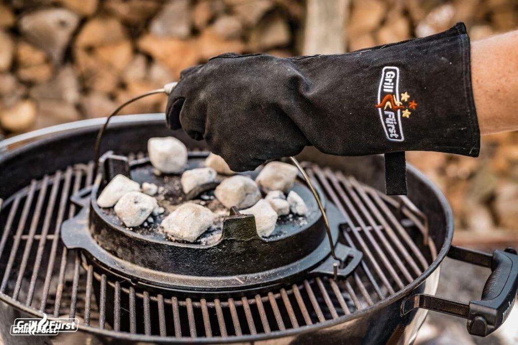 Ohne Grillhandschuhe lässt sich der heiße Dutch Oven nicht anfassen.