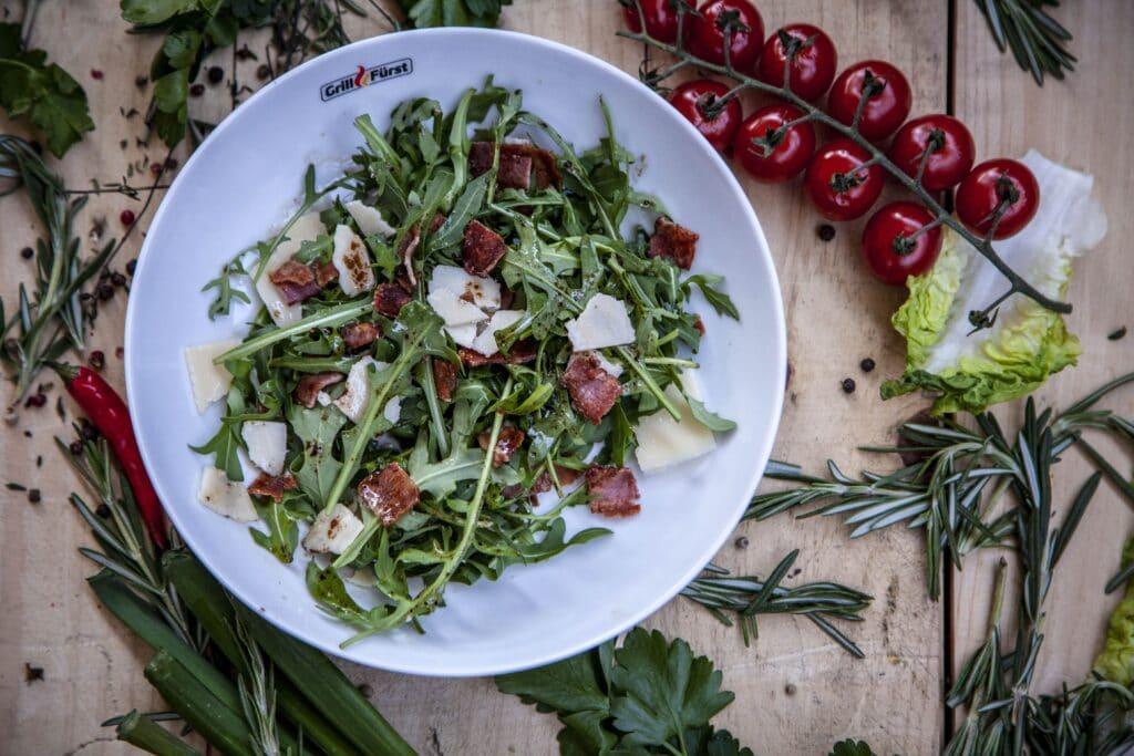 Rucola, Speck, Pinienkerne und Parmesansplitter ergeben einen gesunden Salat als Beilage.