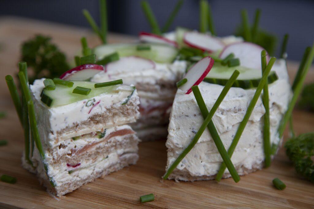 Die Salattorte mit Räucherlachs kann mit Kräutern und Gemüse verschönert werden.