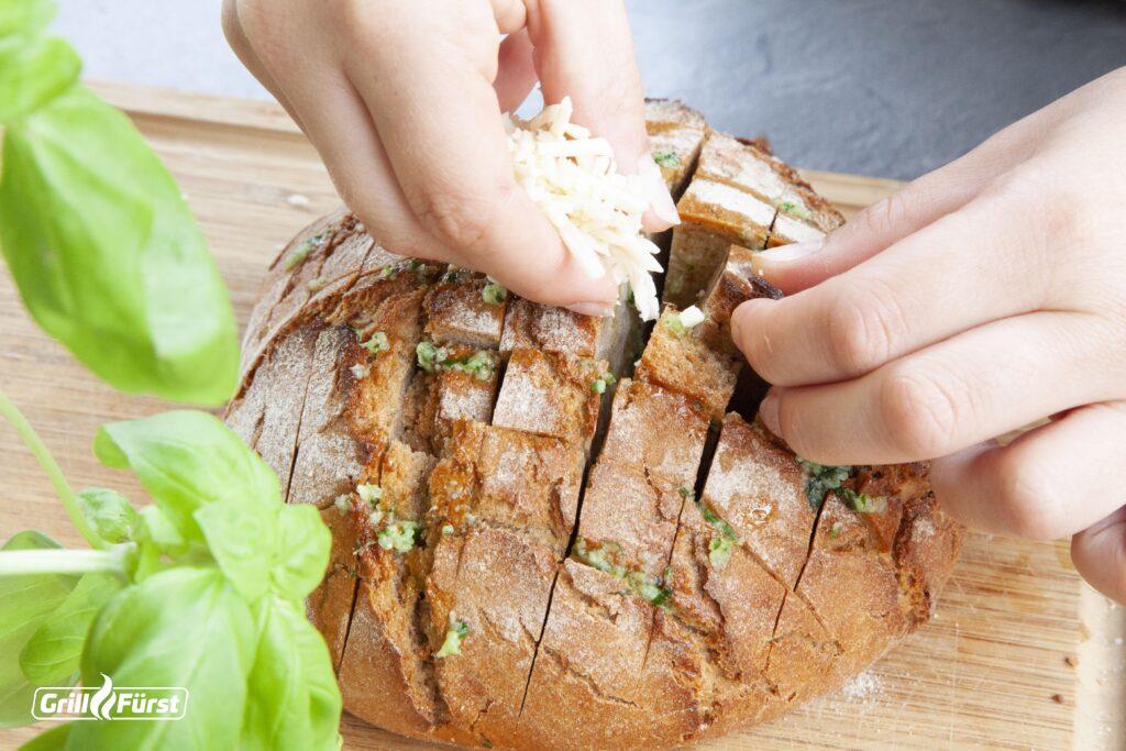 Knoblauchbutter und Mozzarella werden in die Schnittstellen des Brotes gefüllt.