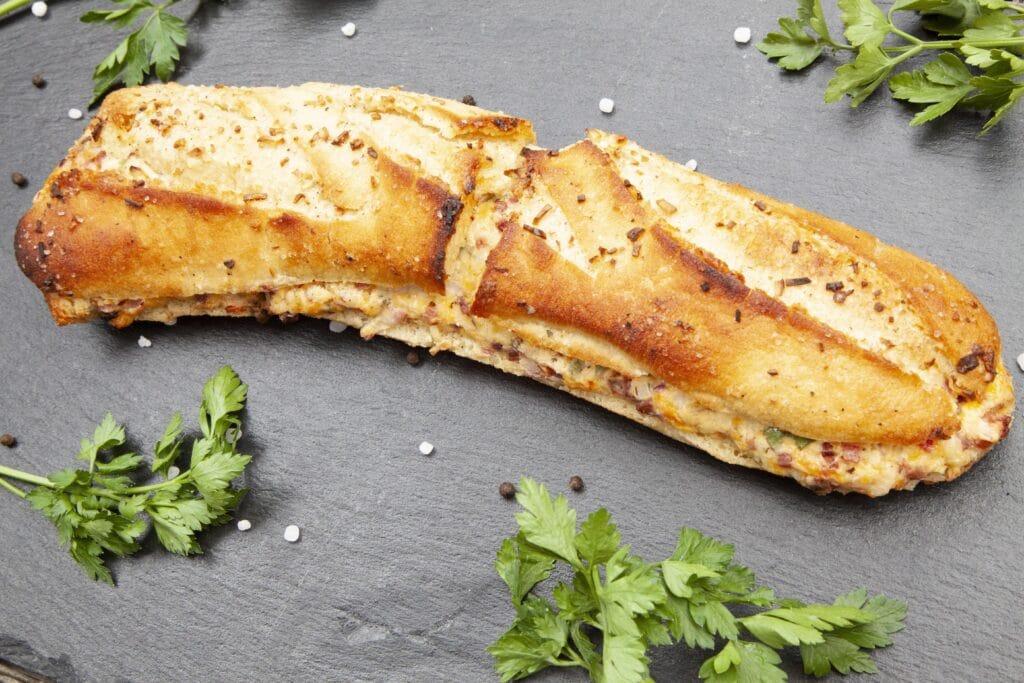 Das Knoblauch-Schinken-Baguette mit dreierlei Käse ist herzhaft und würzig.