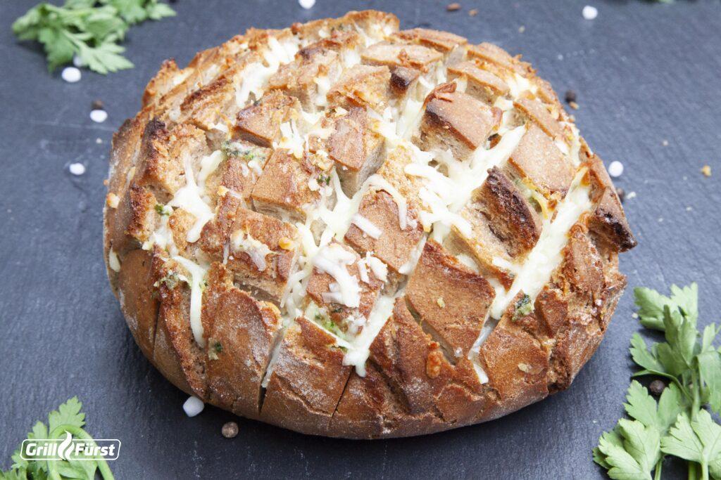 Das Zupfbrot ist gefüllt mit Mozzarella und eine Mischung aus Butter, Olivenöl, Knoblauch und Petersilie.