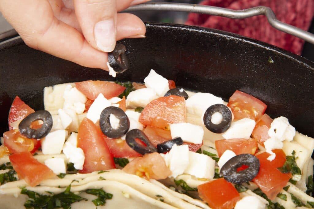 Das Pull-Apart-Brot wird mit Tomaten, Oliven und Mozzarella bestreut.
