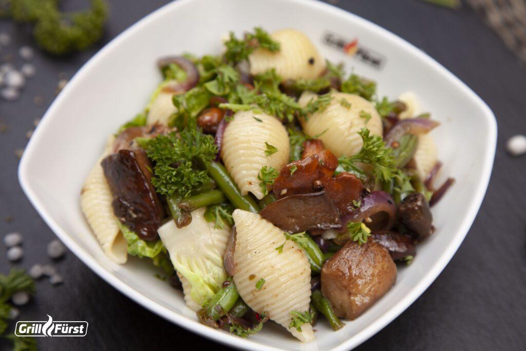 Der Nudel-Pilz-Salat wird mit grünen Bohnen und Romanasalat serviert.
