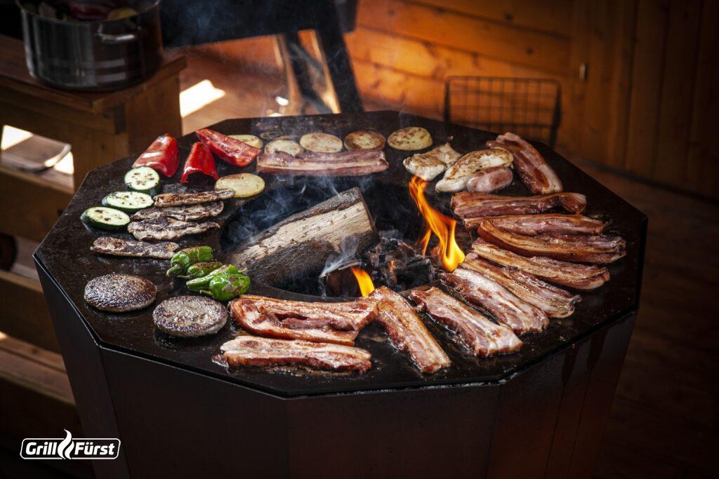 Auf der Feuerplatte werden Gemüse, Bauchscheiben und andere Grillspezialitäten zubereitet.
