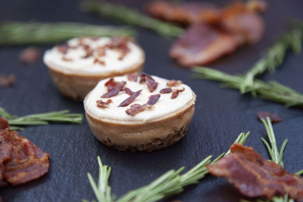 Käsekuchen in Muffinform getoppt mit Puderzuckerglasur und Bacon.