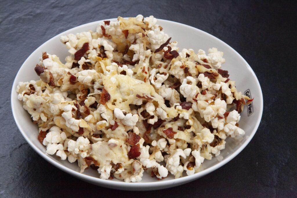 Popcorn wird mit Bacon und Käse überbacken und in einer Schale serviert.