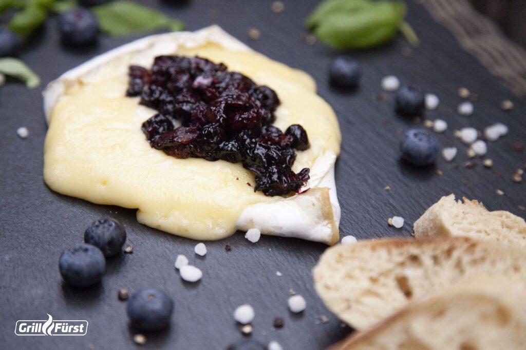 Brie mit Blaubeer-Bacon-Topping schmeckt besonders gut mit frischem Baguette.
