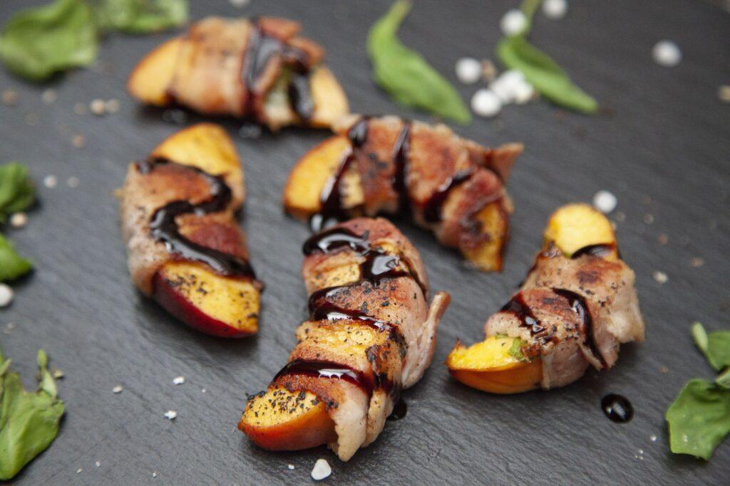 Pfirsichstücke mit Bacon vom Grill werden mit Balsamico-Dressing garniert.