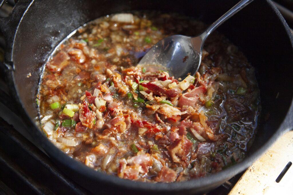 Für die Bacon-Marmelade dürfen sie Zutaten in einem Topf über dem Grill eine Weile kochen.