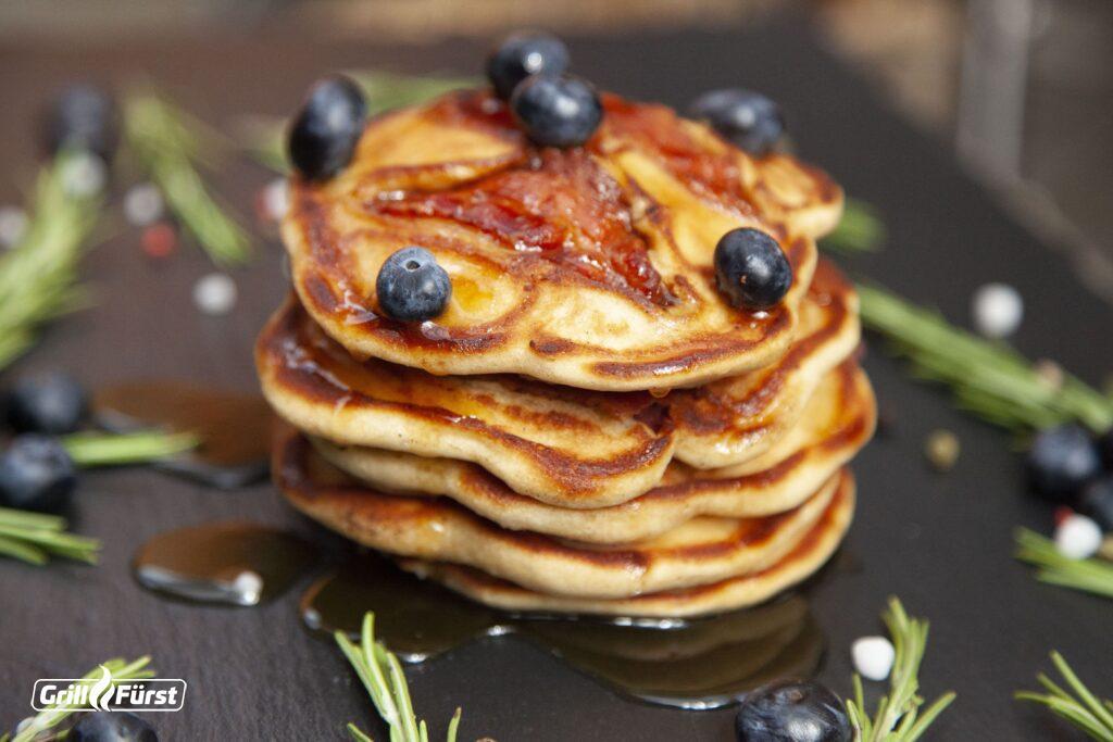 Roggenpancakes mit Bacon werden mit Ahornsirup und Blaubeeren serviert.
