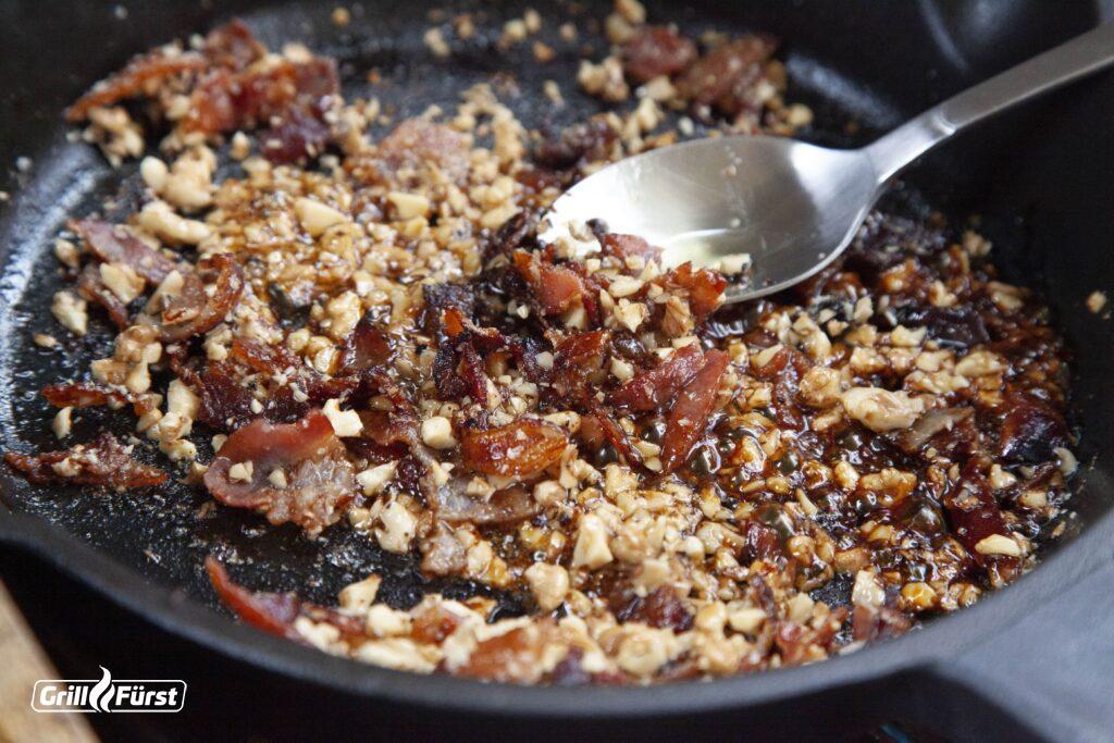 Walnüsse und Baconstückchen werden auf dem Grill zusammen zubereitet.