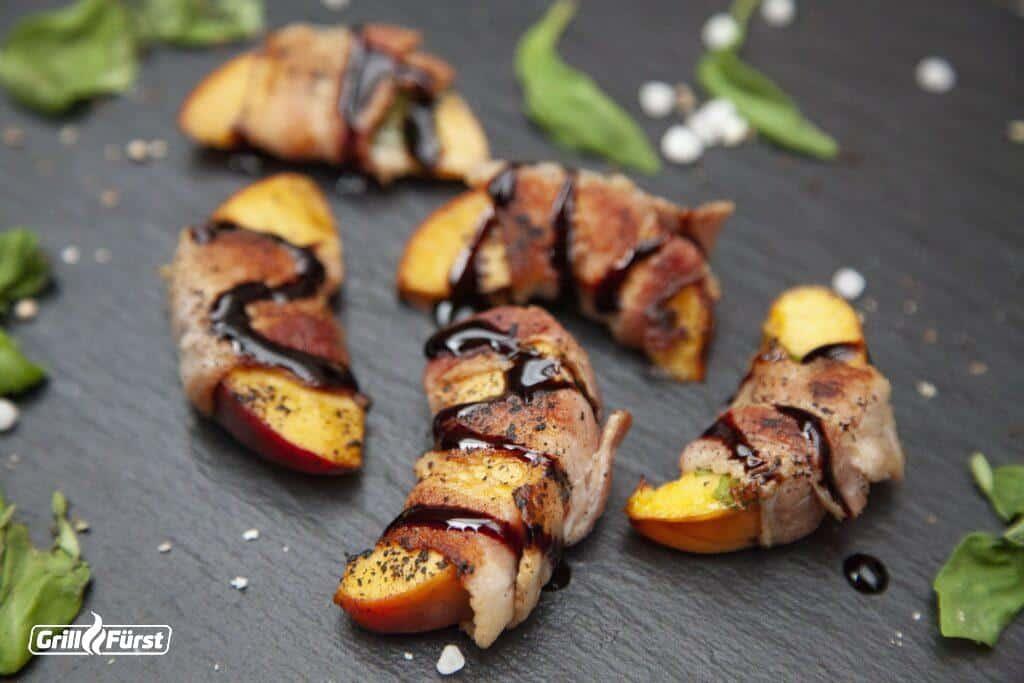 Gegrillte Pfirsichstücke mit Bacon umwickelt