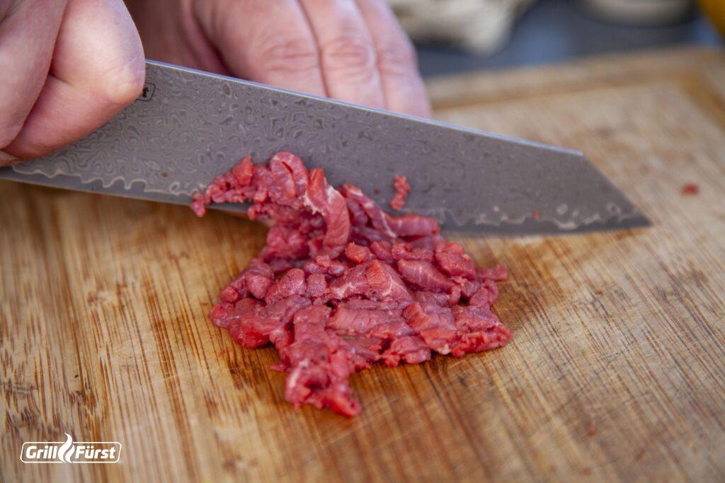 Auf einem Holzbrett wird rohes Fleisch zubereitet.