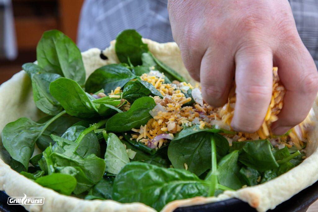 Die Spinat-Quiche wird mit einer Mischung aus Walnüssen und geriebenem Cheddar bestreut und anschließend überbacken.