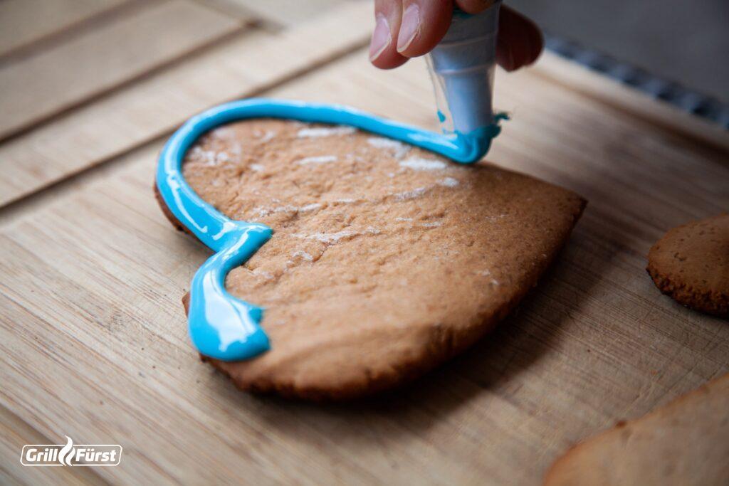 Lebkuchenherzen werden mit Zuckerguss verziert.