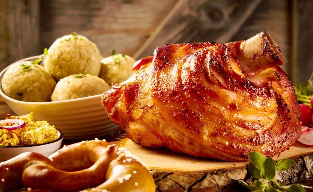 Schweinshaxe mit schöner Kruste wird mit Knödeln und anderen Leckereien serviert.