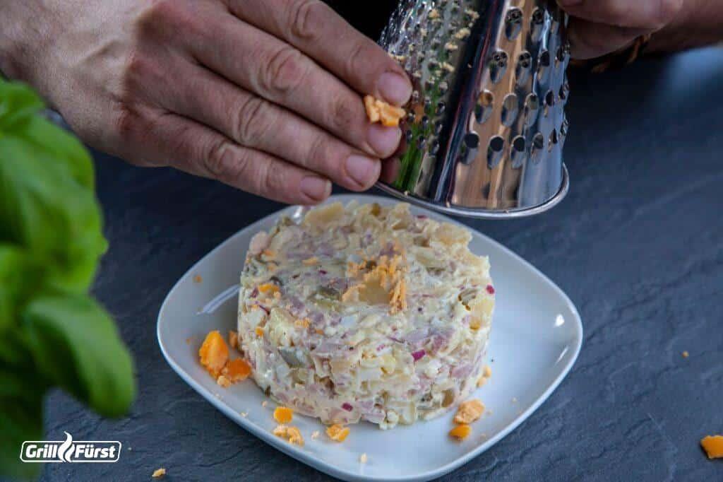Gekochtes Eigelb über die Kartoffelsalattorte reiben
