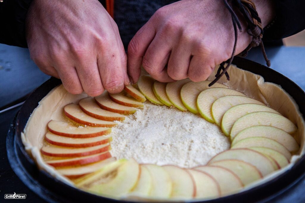 Apfelkuchen wird im Dutch Oven Deckel mit Apfelscheiben belegt.
