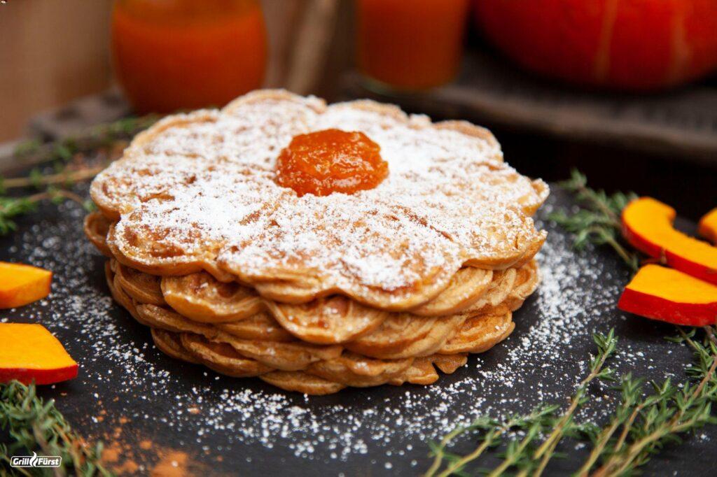 Kürbiswaffeln werden mit Puderzucker und einem Klecks Apfel-Kürbis-Marmelade serviert.