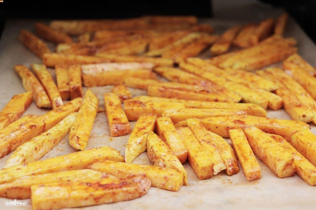Gewürzte Kürbispommes werden im Grill zubereitet.