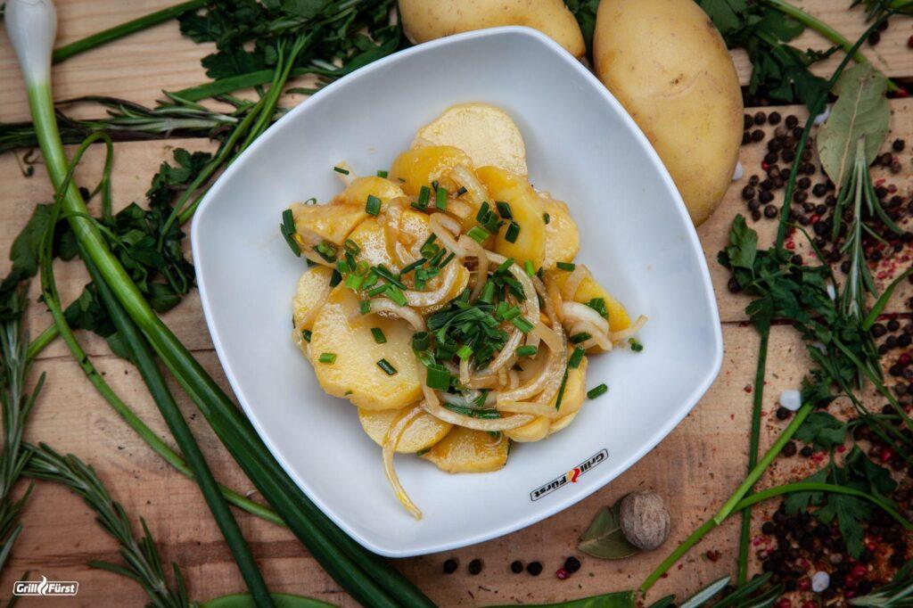 Kartoffelsalat mit Zwiebeln, Essig, Öl und Kräutern