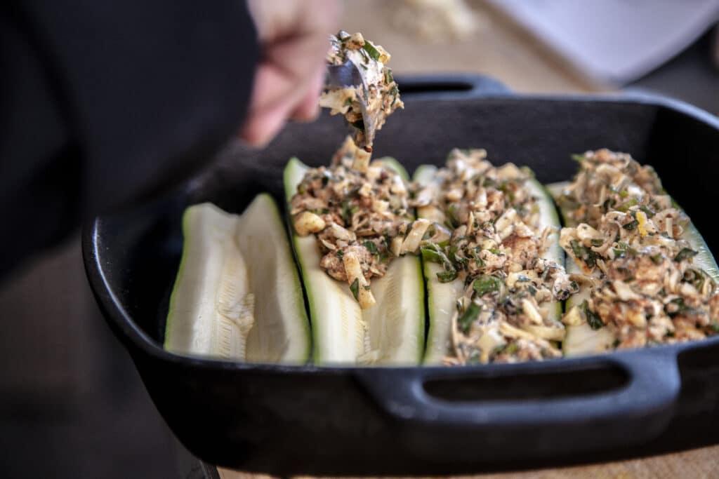 Zucchini-Schiffchen werden mit der Kräutermischung befüllt