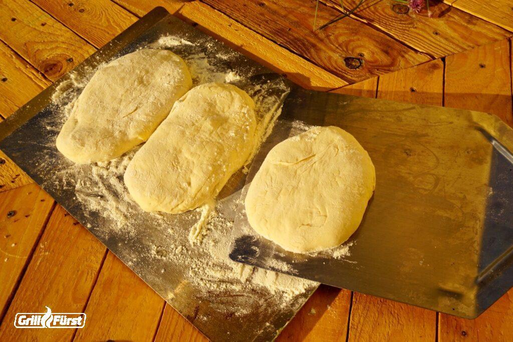 Pide Fladen werden mit einem Pizzaheber angehoben.