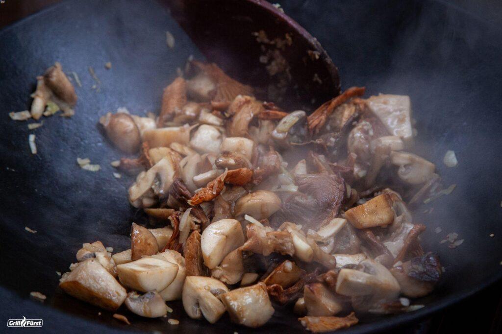 Pilze werden im Wok angedünstet.