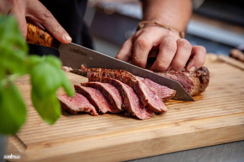 Steak auf einem Brett in Scheiben geschnitten.