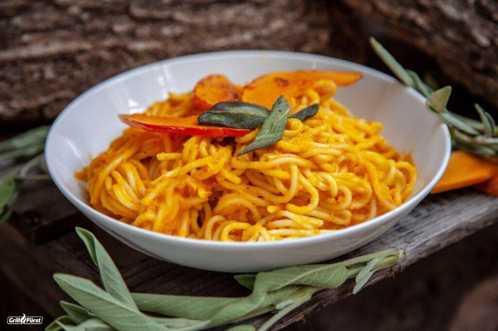 Die Spaghetti werden mit Kürbissoße, Kürbisstückchen und Salbeiblättern serviert.