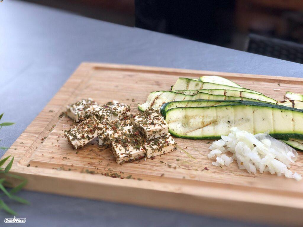 Fertig zubereiteten Fetastücke und gegrillte Zucchini Scheiben