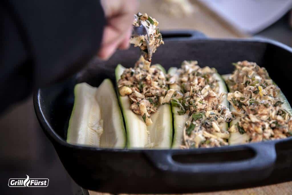 ausgehöhlten Zucchinihälften mit der Kräutermischung füllen
