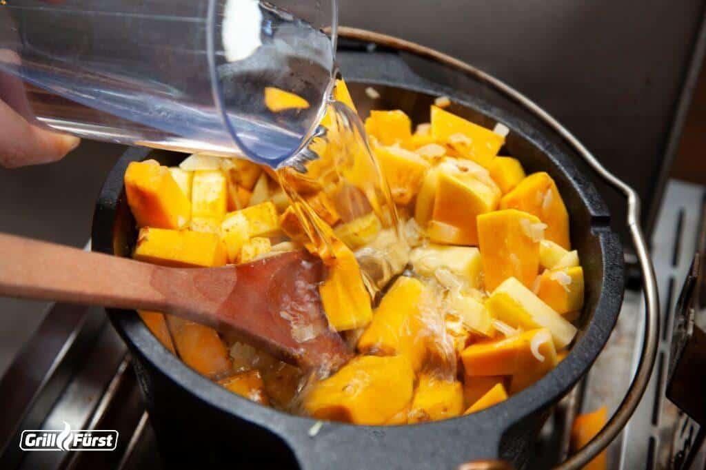 Kürbisstücke im Dutch Oven mit Wasser übergießen