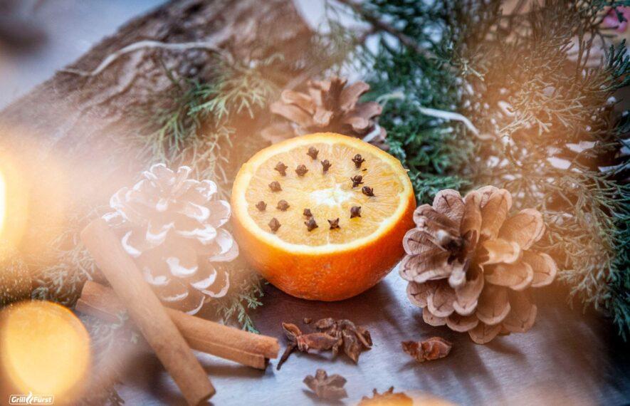 Aufgeschnittene Orange mit Zimt, Nelken und Tannenzapfen