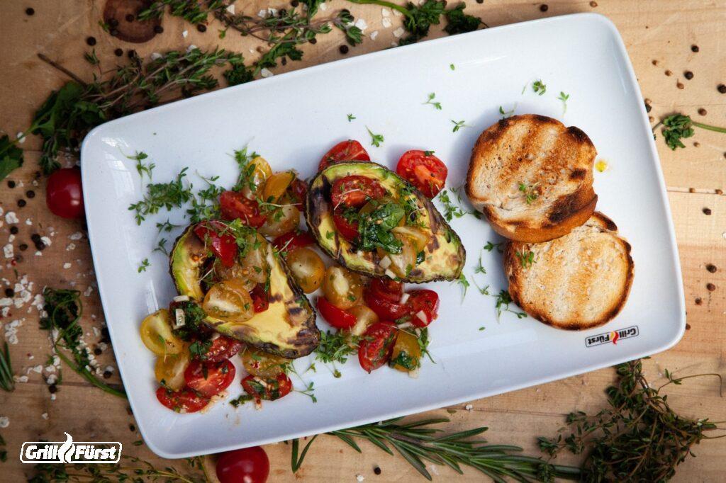 Avocado belegt mit Tomaten und Kräutern, daneben Baguette