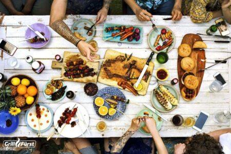 Gedeckter Tisch mit Grillfleisch, Gemüse und Co.