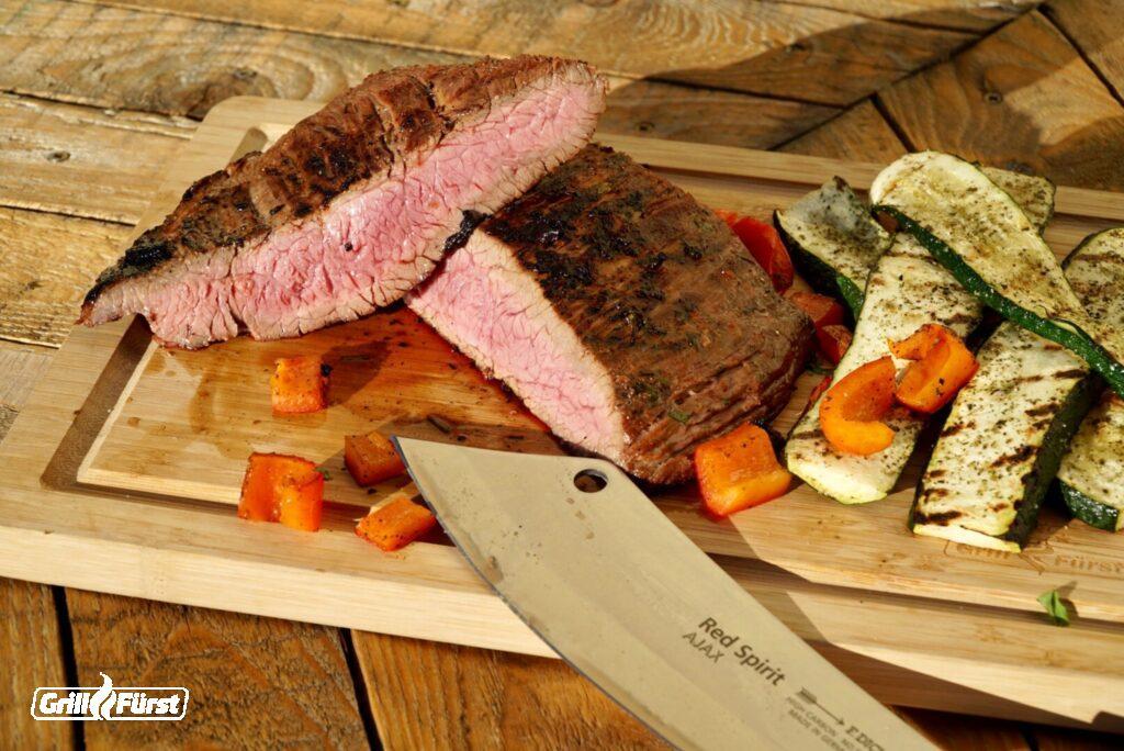 Flank Steak marinieren, rosa gegrillt  und aufgeschnitten mit Zucchini und Möhren auf Holzbrett
