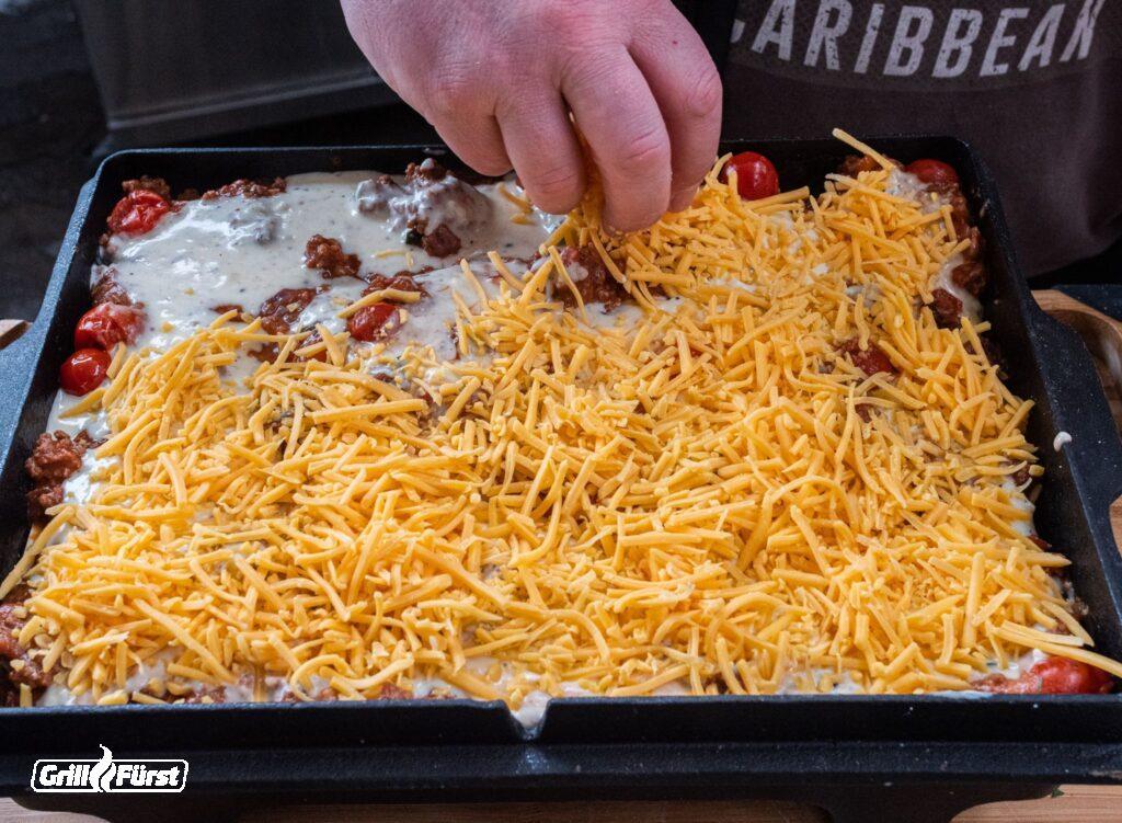 Käse auf Lasagne streuen