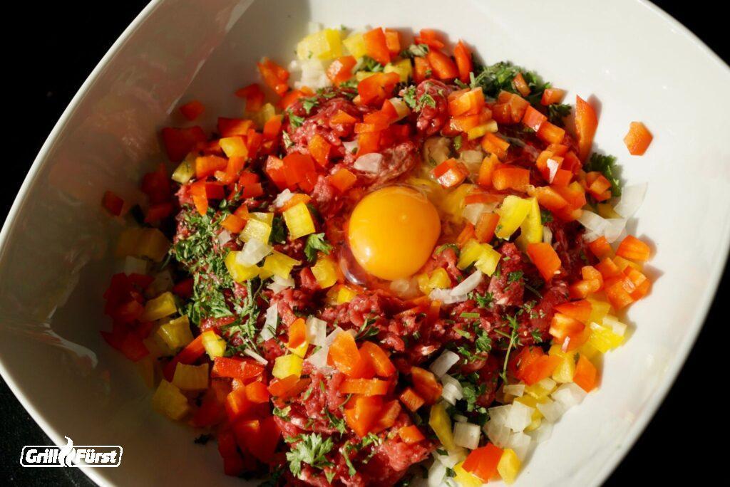 Hackfleisch, Ei, Paprikawürfel, Zwiebelwürfel und Kräuter in Schüssel