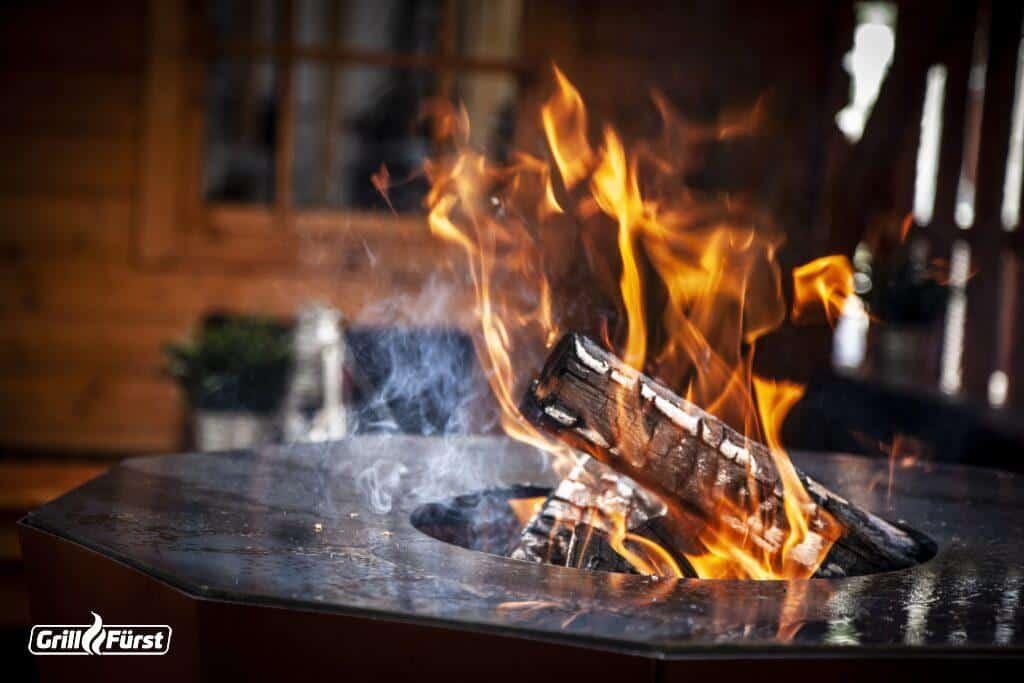 Feuertonne mit angezündetem Holz und Feuer