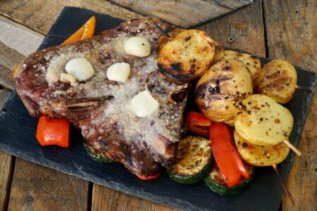 Gegrillte Kartoffelspieße neben gesalzenem Fleisch mit Knoblauchzehen
