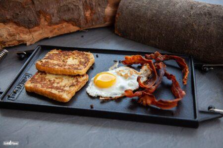 So gelingt ein leckeres Frühstück: Auf der glatten Seite der Grillplatte kannst du Spiegeleier, Bacon und Toast ganz einfach zubereiten.